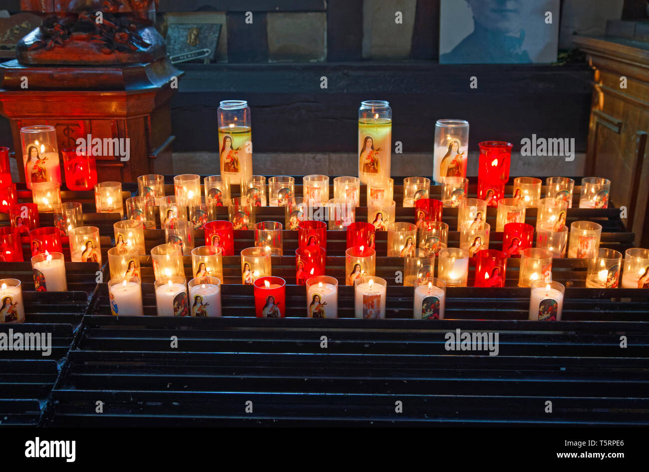 lighted votive candles, warm glow, petition, St. Catherine Church, Catholic, old religious building, Europe, Normandy; Honfleur; France; summer, horiz - Stock Image