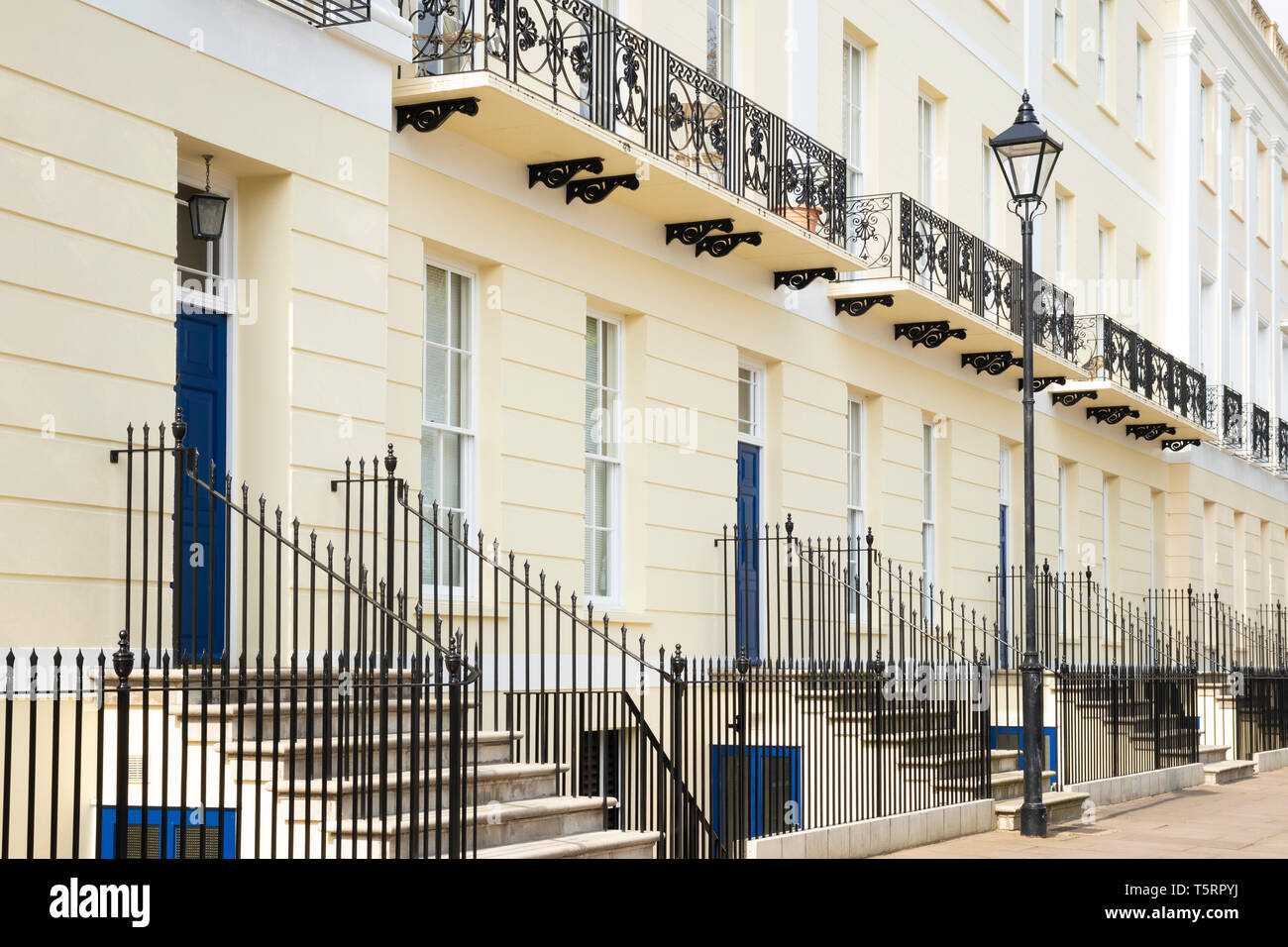Blue doors and ornate iron wrought balconies on a Terrace of Georgian houses Imperial Square Cheltenham Spa Gloucestershire England GB UK Europe - Stock Image