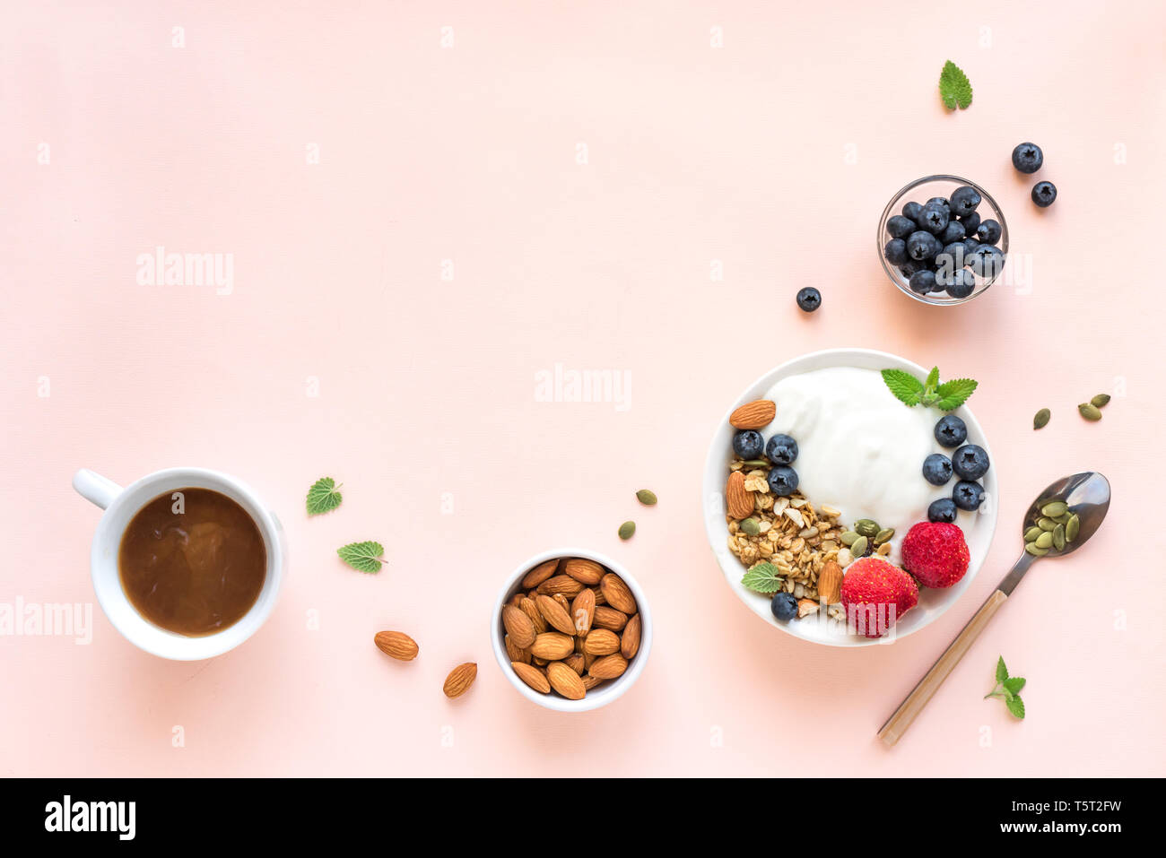 Greek yogurt with homemade granola and berries for healthy breakfast on pink pastel background, top view, copy space. Stock Photo
