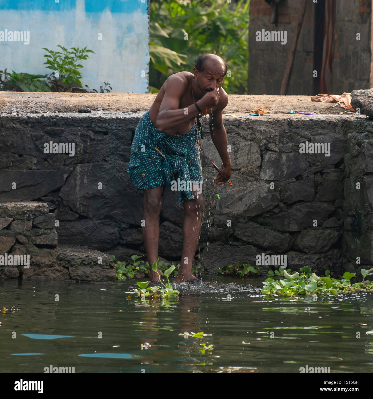 Square portrait of a man having a wash on the riverbank in Alleppy, India - Stock Image