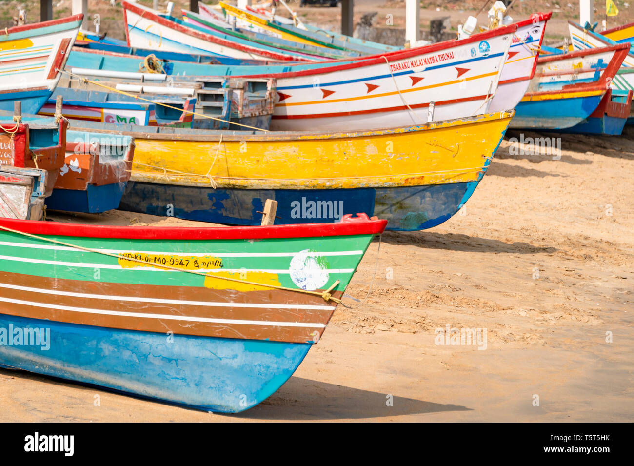 Horizontal view of colourful fishing boats at Vizhinjam in Kerala, India. - Stock Image
