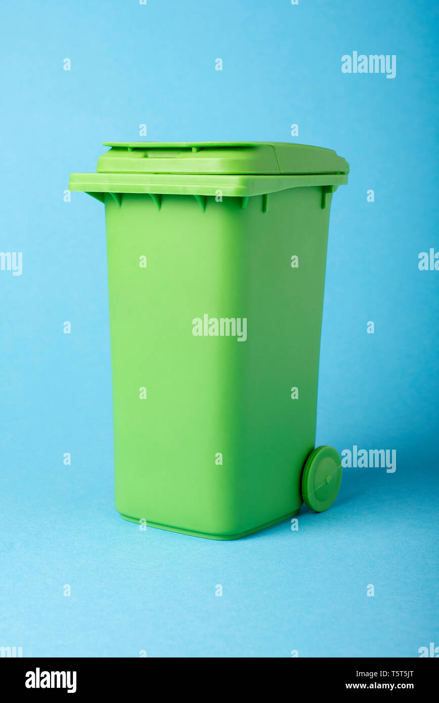 Green dustbin on a blue background. Recycling. Materials for recycling and reuse on a blue background. Ecological concept. - Stock Image