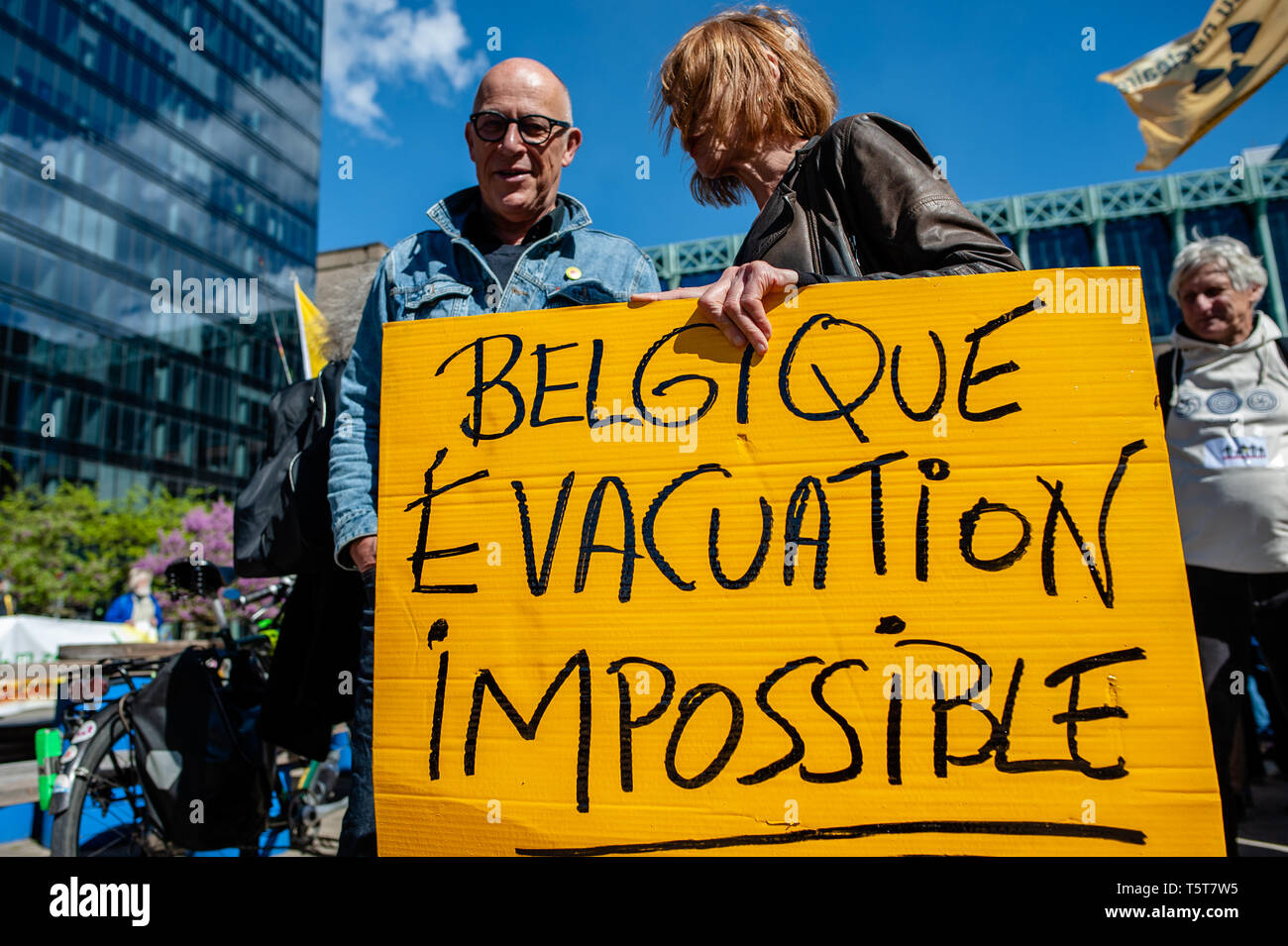"""A couple seen holding a placard during the protest. On the day that commemorates the 33rd anniversary of the Chernobyl nuclear disaster, a protest was organized by the """"Fin du nucléaire"""" and Réveil Anti-Nucléaire"""" associations, as well as director Bouli Lanners. They want the five most dangerous Belgian reactors to be shut down. - Stock Image"""