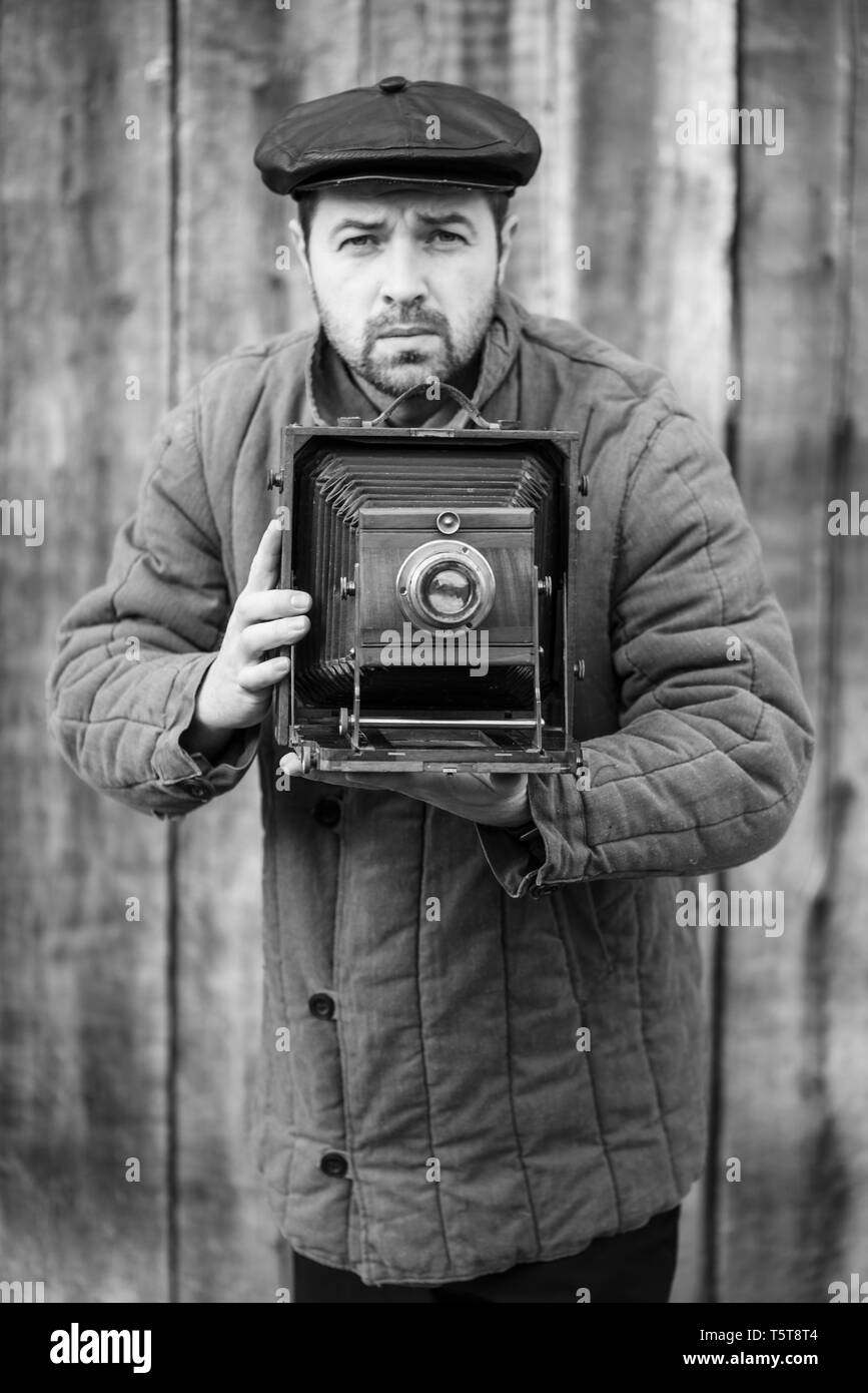 Photographer prepares for shooting on large format camera. Concept - photography of the 1930s-1950s, monochrome Stock Photo