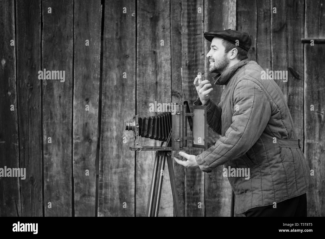 Old fashioned photographer asks for a smile. Works on large format camera. Concept - photography of the 1930s-1950s - Stock Image