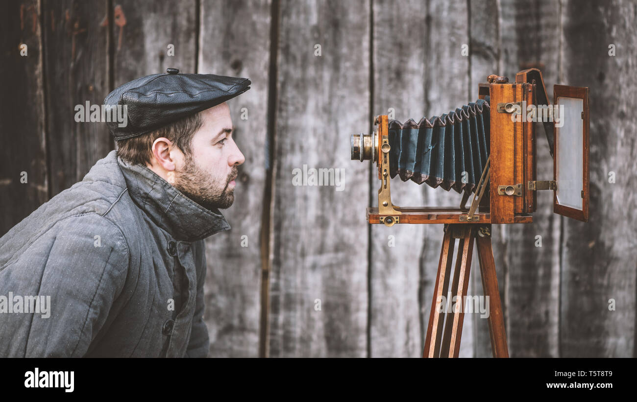 Selfie of old fashioned man on large format camera. Idea - self-portrait - Stock Image