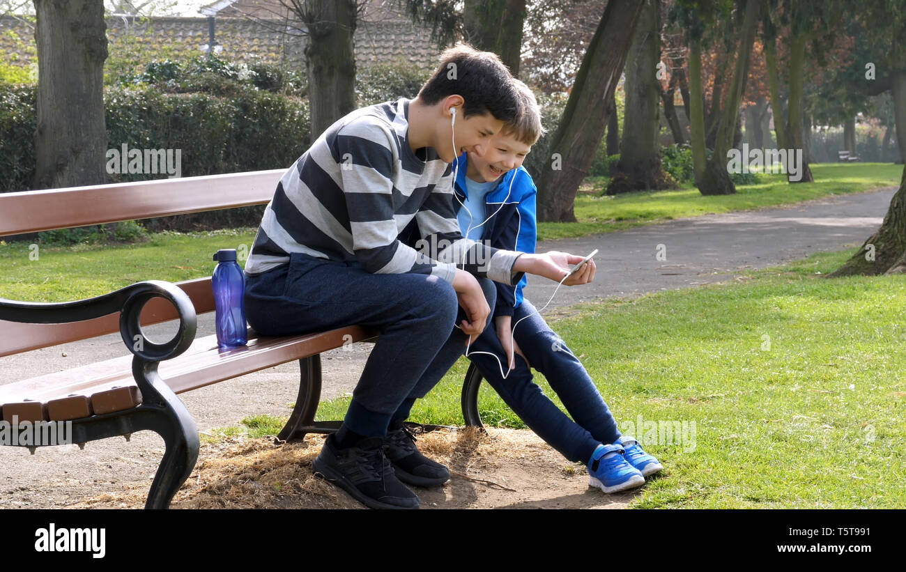 teen boys with smart phone listening or talking in british park on bench. teenager and social media concept. - Stock Image