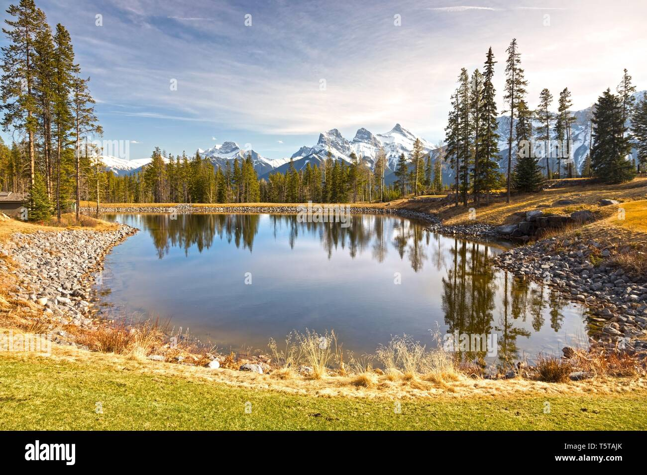 Scenic Springtime Landscape View Mountain Peaks, Green Grassland, Blue Lake Canmore Alberta, Canadian Rockies Foothills Banff National Park - Stock Image