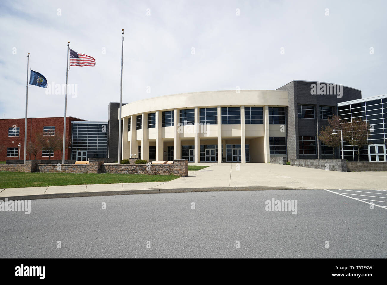 Exterior of a modern school building with copyspace.  There is an American flag and a Pennsylvania state flag on the flagpoles. - Stock Image
