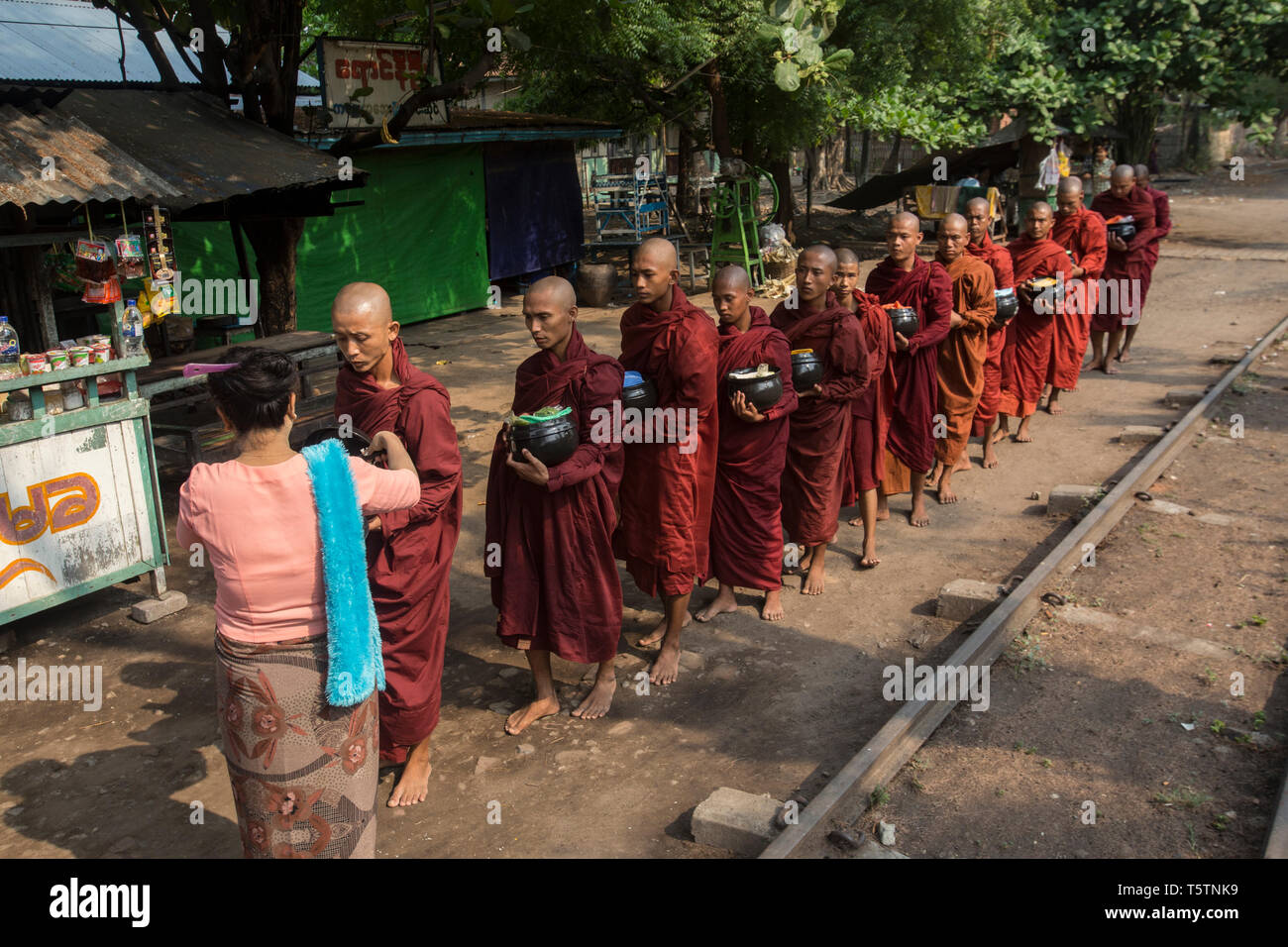 Buddhist monks receiving alms by a railway track in Thazi, Shan State, Myanmar. Stock Photo