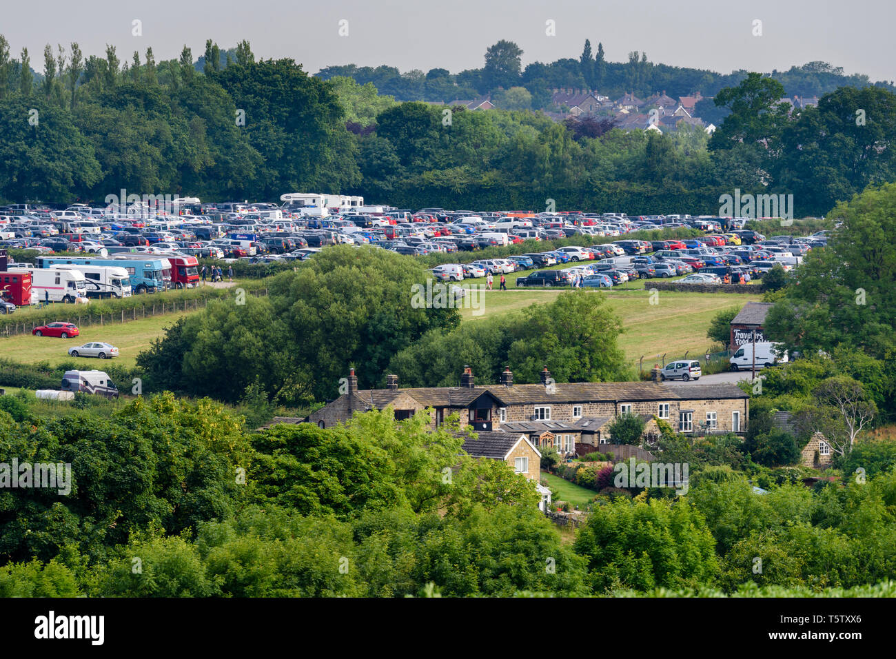 High view of busy showground car park under blue sky in summer (rows of vehicles parked in field) - Great Yorkshire Show, Harrogate, England, UK. - Stock Image