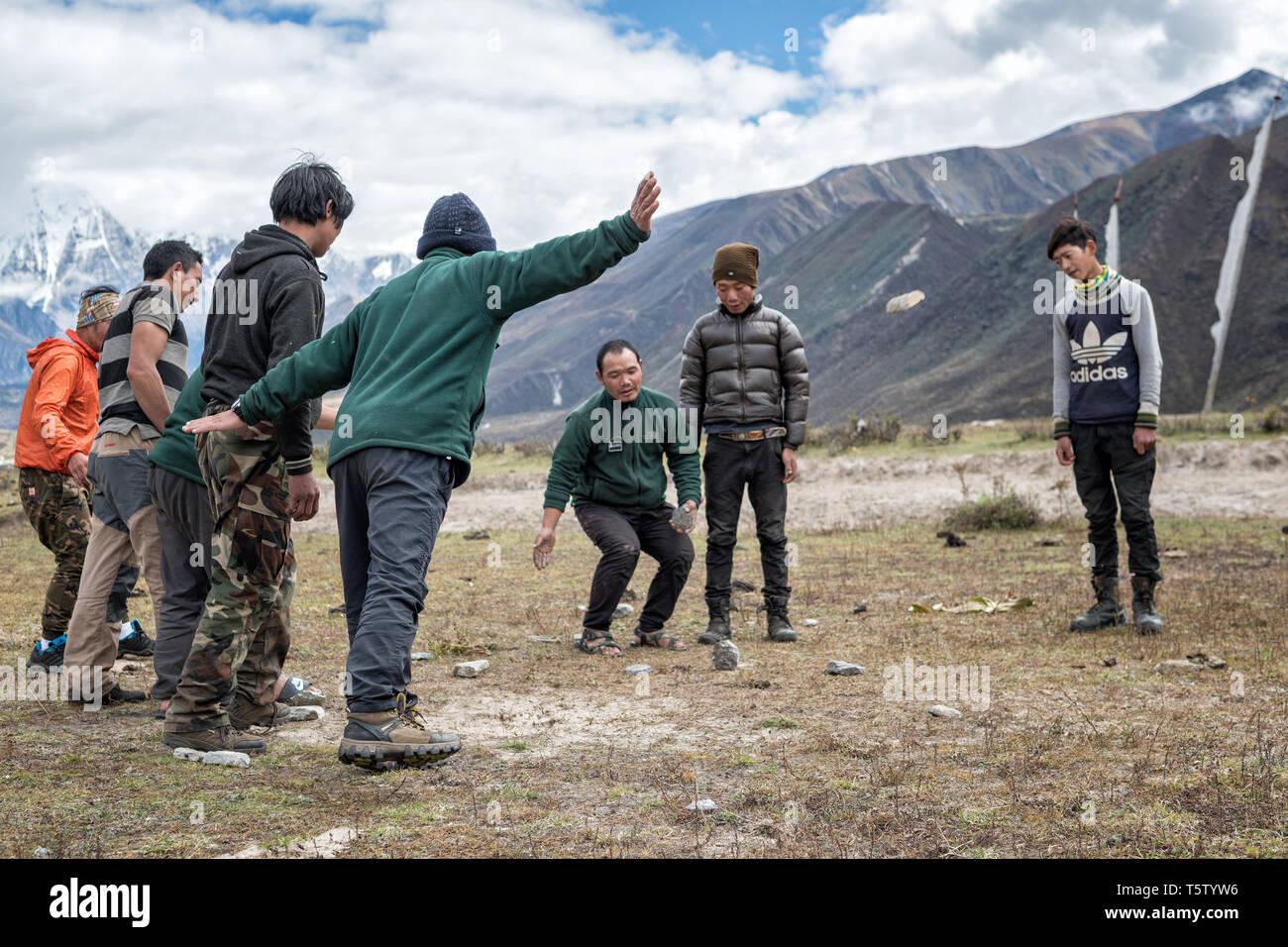 Men playing dego (Traditional Bhutanese game) in Chozo, Lunana Gewog, Gasa District, Bhutan Stock Photo