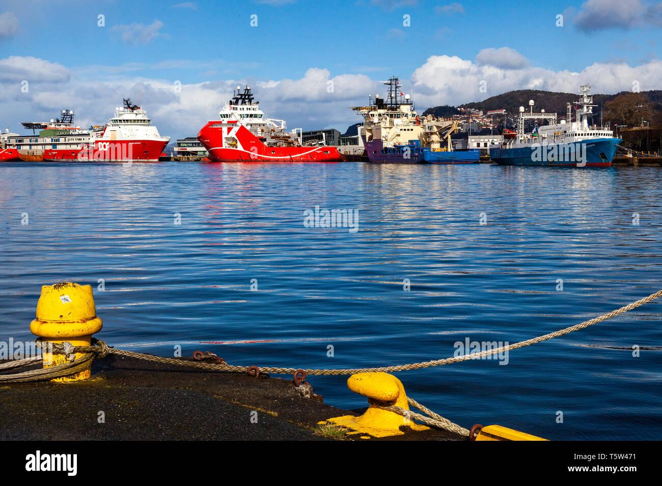 Offshore supply vessels Skandi Bergen, KL Sandefjord and Deep Vision, in port of Bergen, Norway. Skoltegrunnskaien terminal. On right side is resea - Stock Image