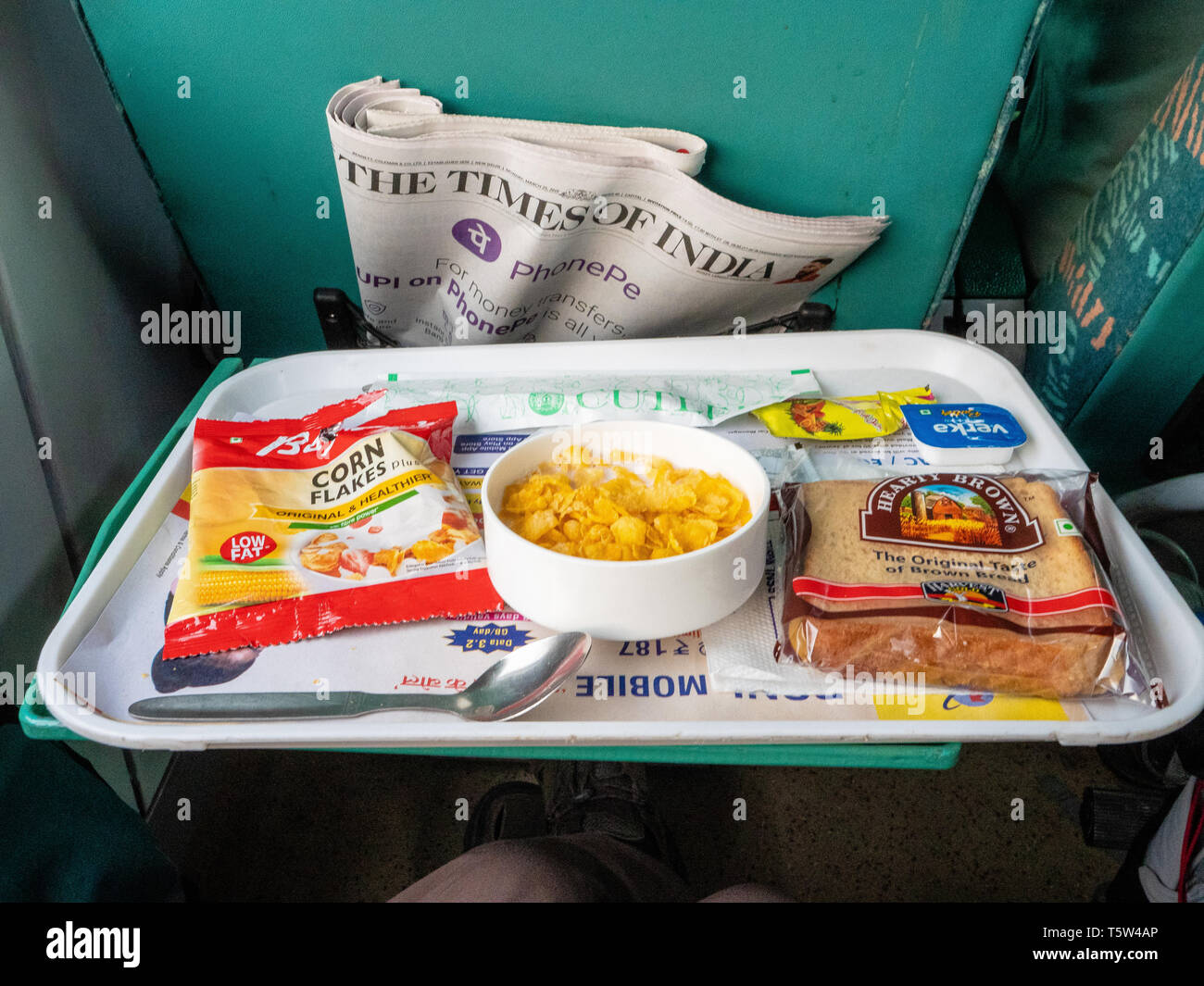 First class seat on Indian Railways express train with a copy of the Indian Times and complimentary breakfast with packeted toast and Corn Flakes - Stock Image