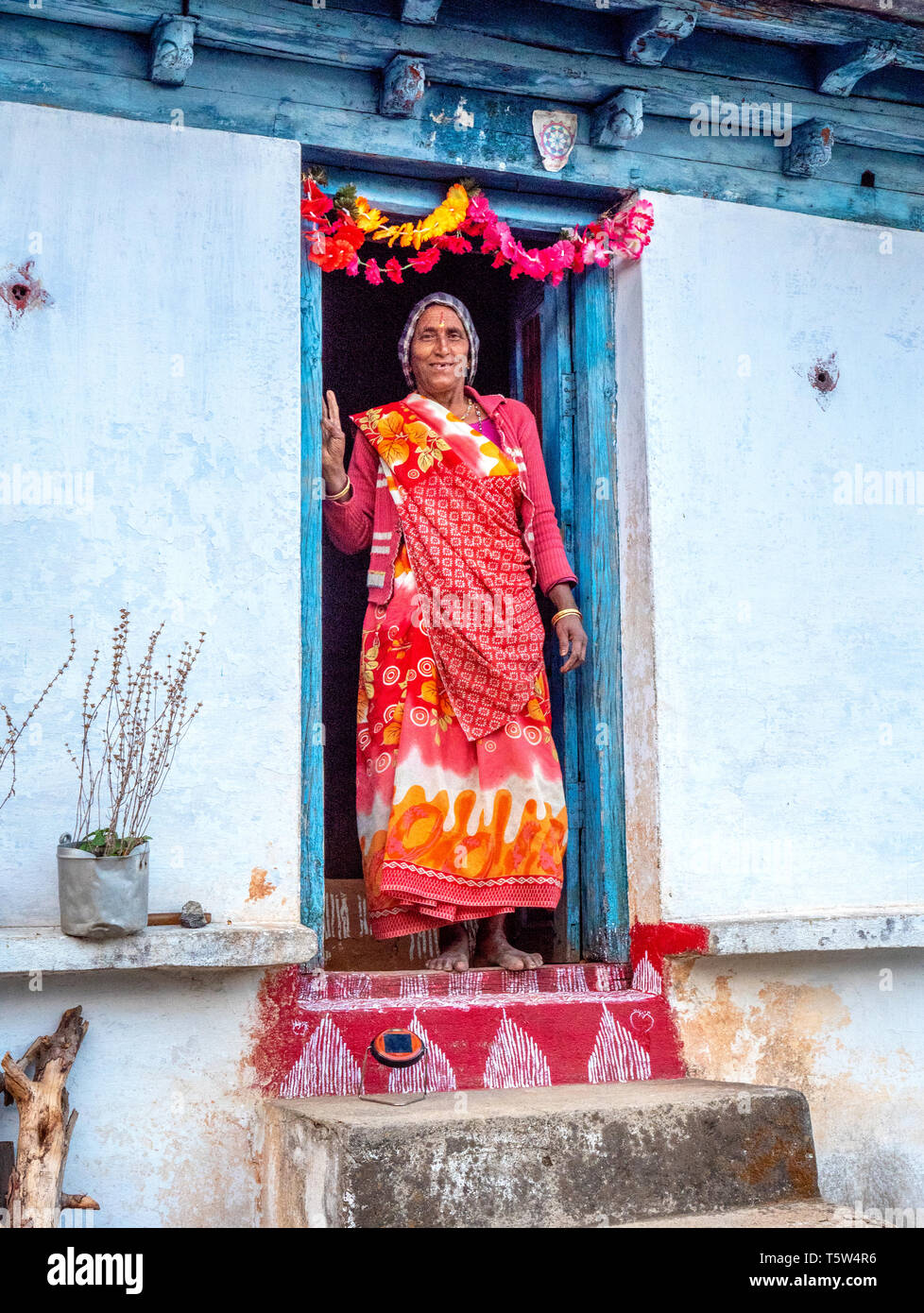 Woman on the decorated and garlanded threshold of her house in the remote village of Satri in the Binsar region of Uttarakhand Himalayas - Stock Image