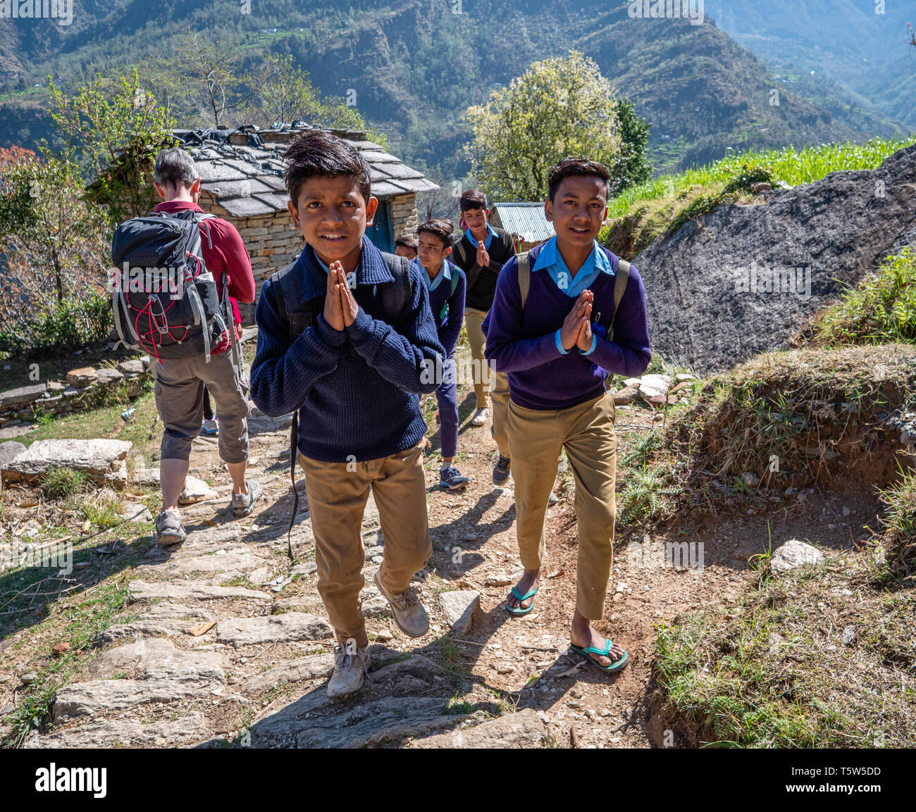 Smartly dressed schoolboys on their way to school giving a polite and prayerful Namaste to passing visitors in Supi village Uttarakhand Northern India - Stock Image