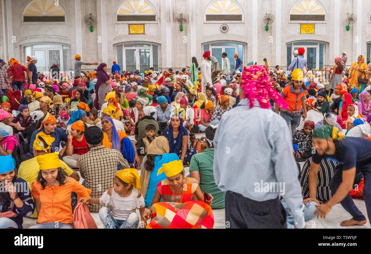 Colourful diners excitedly waiting to be fed in a Sikh temple dining hall in New Delhi Northern India - Stock Image