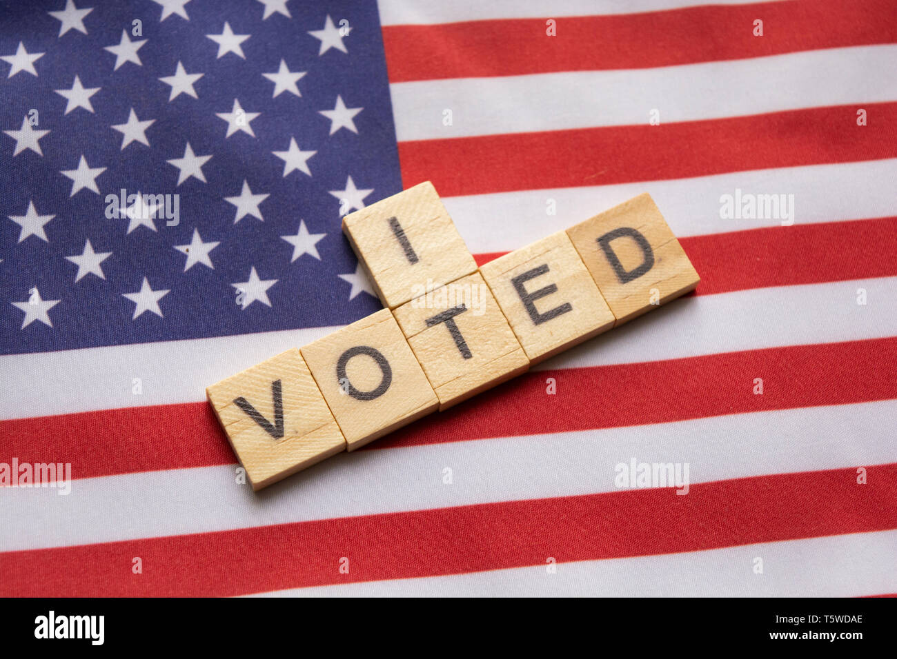 Maski, India 26, April 2019 : I voted wooden block letters,US elections on American flag. - Stock Image