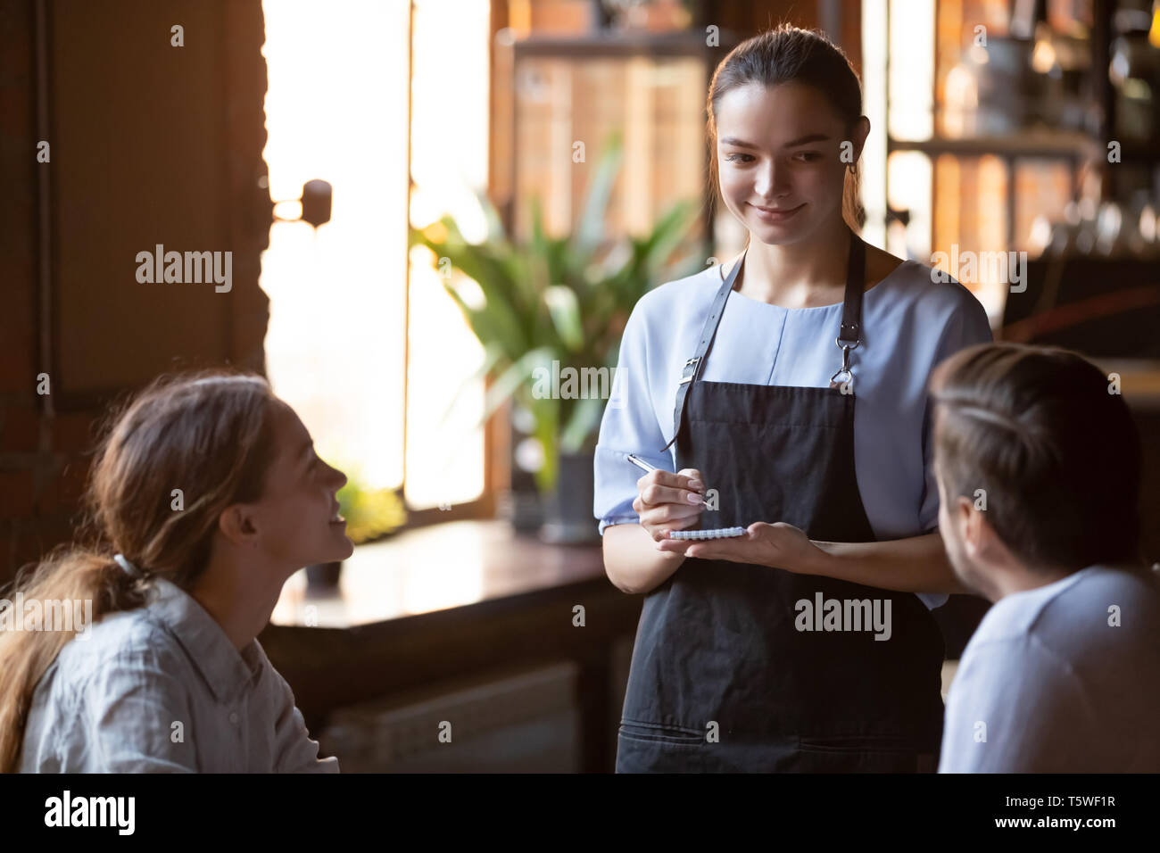 Smiling waitress serving a married couple take order - Stock Image