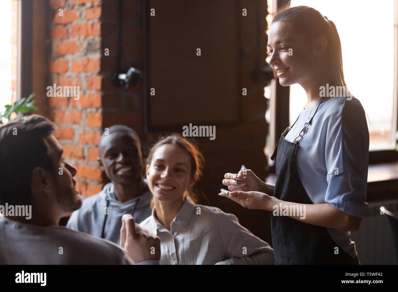 Diverse cheerful friends making order talking with waitress girl - Stock Image