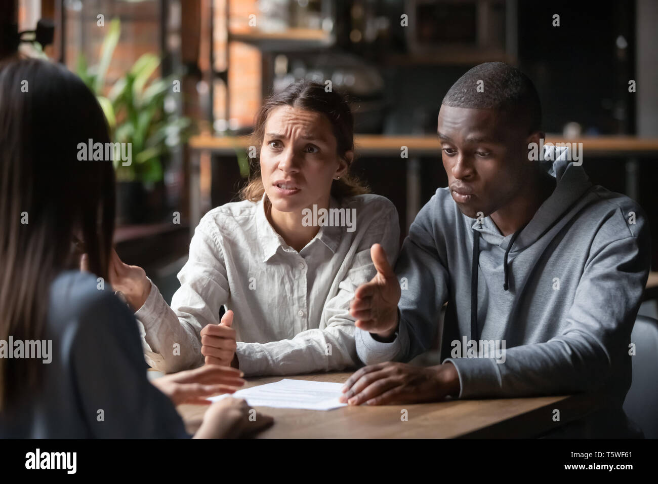 Diverse family couple clients having claim about contract conditions - Stock Image