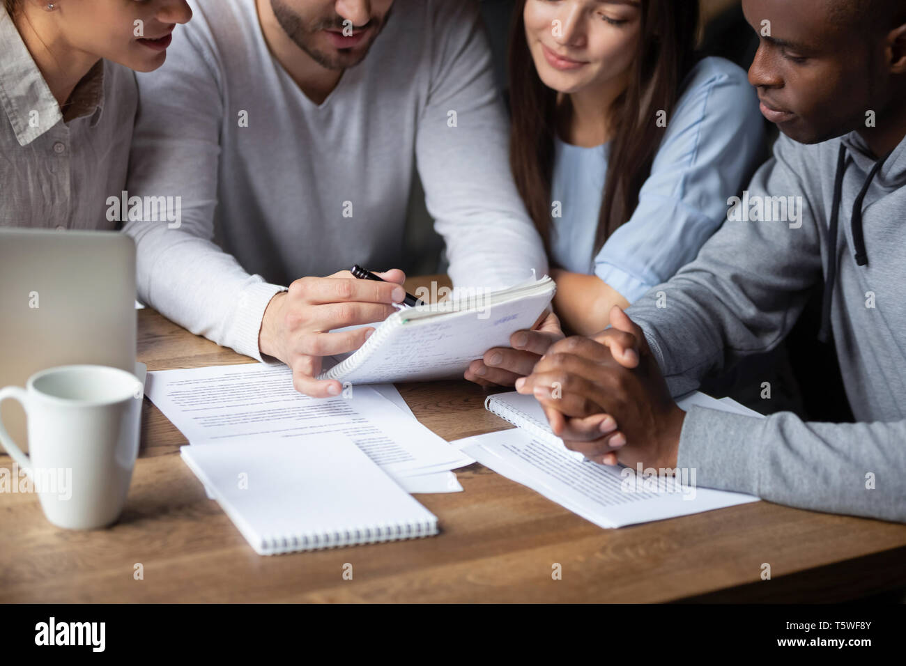 Different ethnicity millennial teammates sitting at table study together - Stock Image