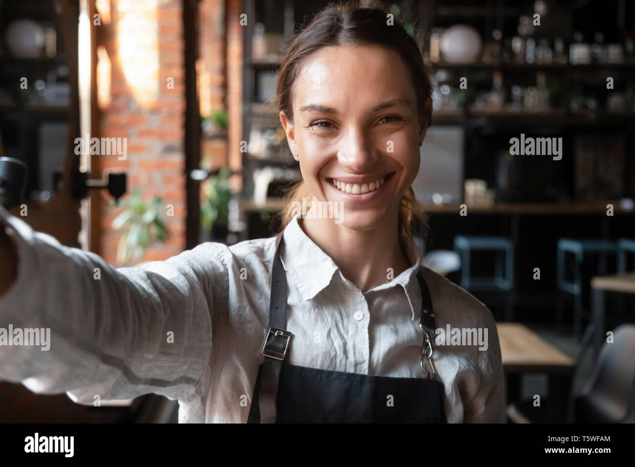 Mixed race female in apron smiling looking at web camera - Stock Image