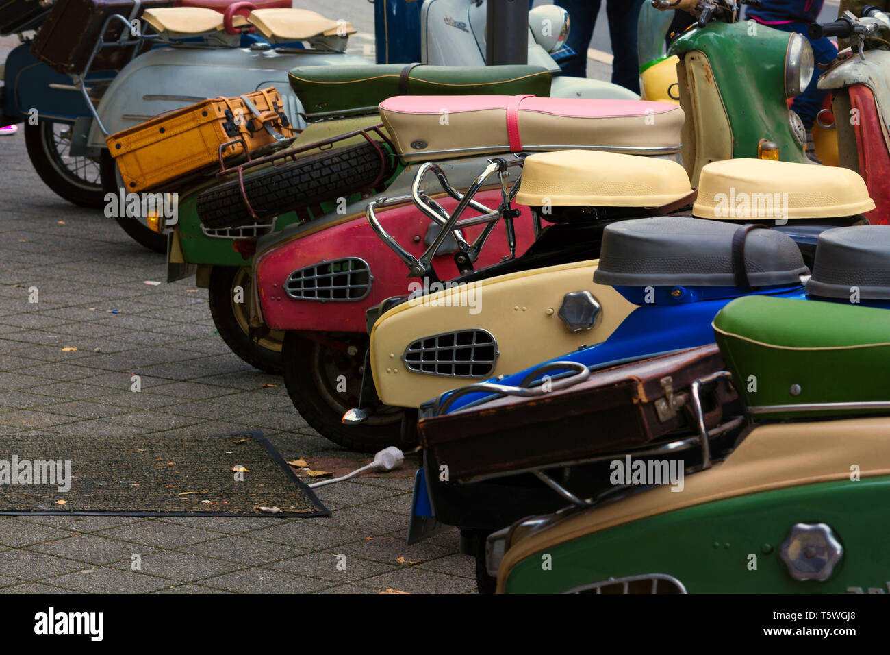 Various retro scooters line the road in a row. - Stock Image