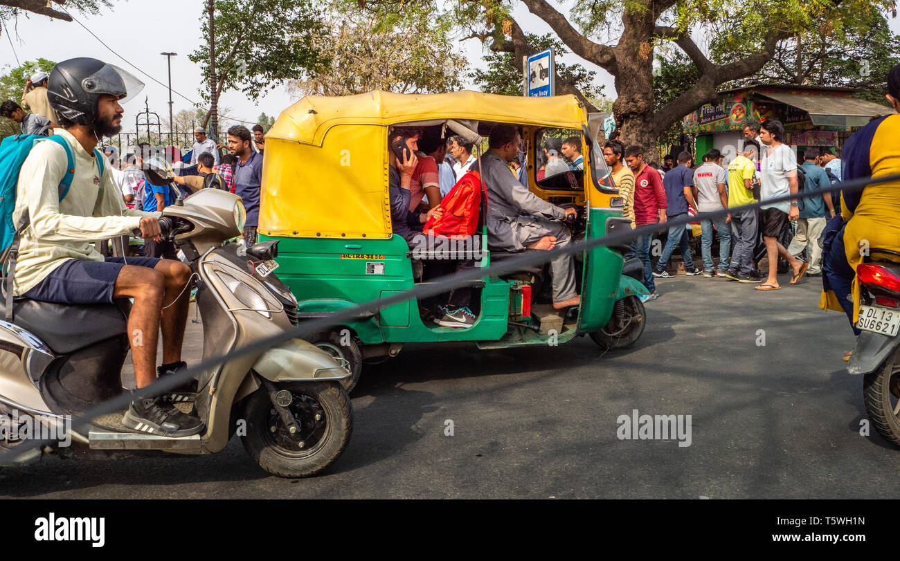 Driving in Delhi - heavy traffic  is the norm with tuk-tuks, cars, motorbikes, lorries and pedestrians competing for space - shot from a car window - Stock Image
