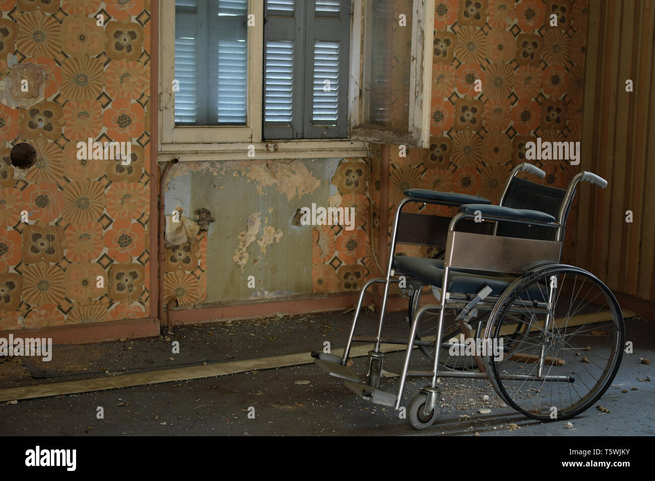 Vintage wheelchair peeling wall and dusty floor in old abandoned house. - Stock Image