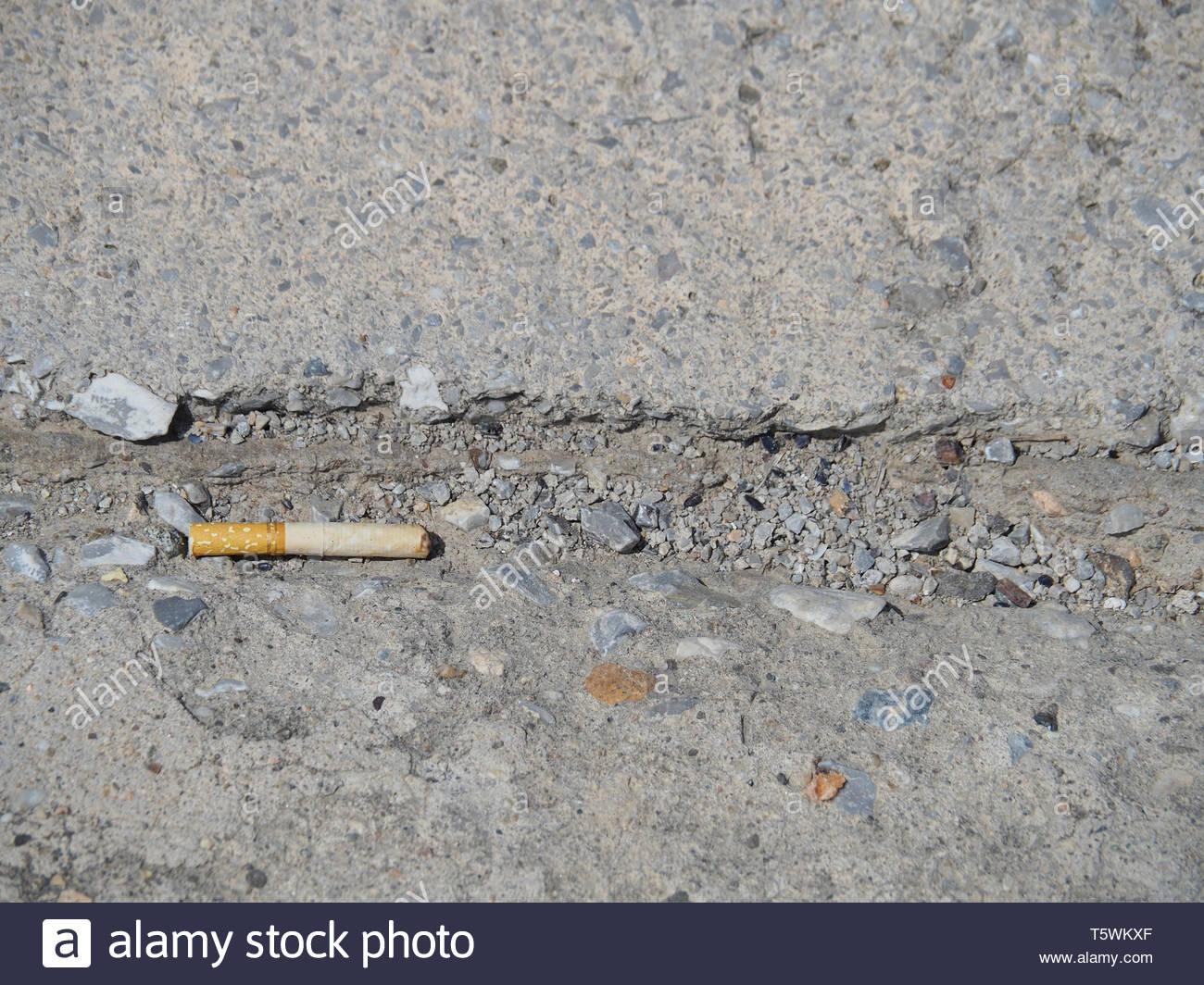 cigarette bud on the sidewalk - Stock Image