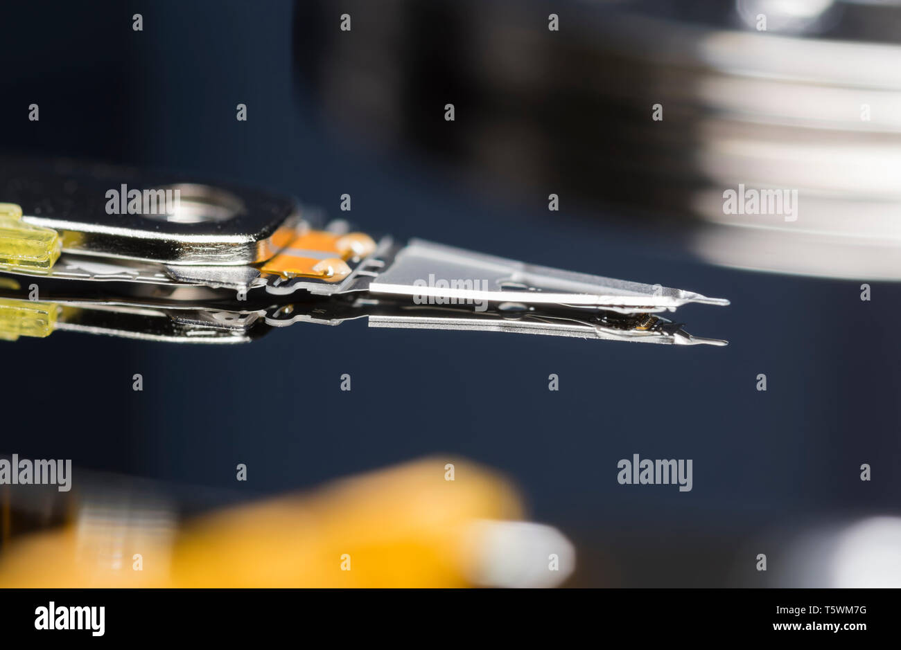 Macro closeup image of the actuator arm and read / write head reading and writing data from and to a computer hard disk drive (HDD) platter. - Stock Image