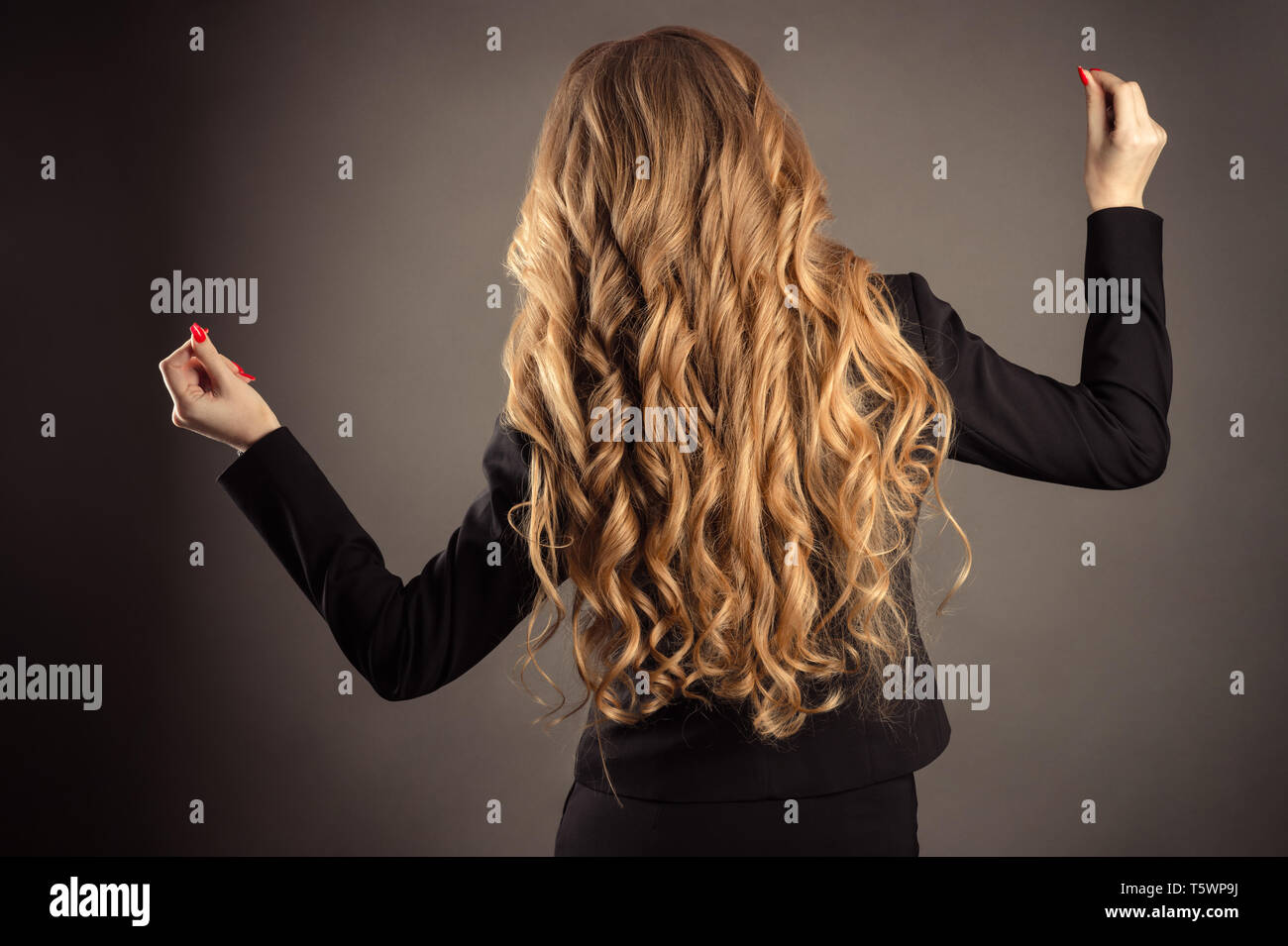 successful business woman with gorgeous wavy hair - Stock Image