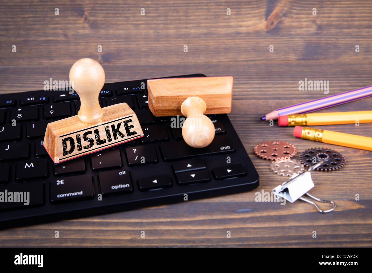 Dislike concept. Computer keyboard and wooden stamps - Stock Image