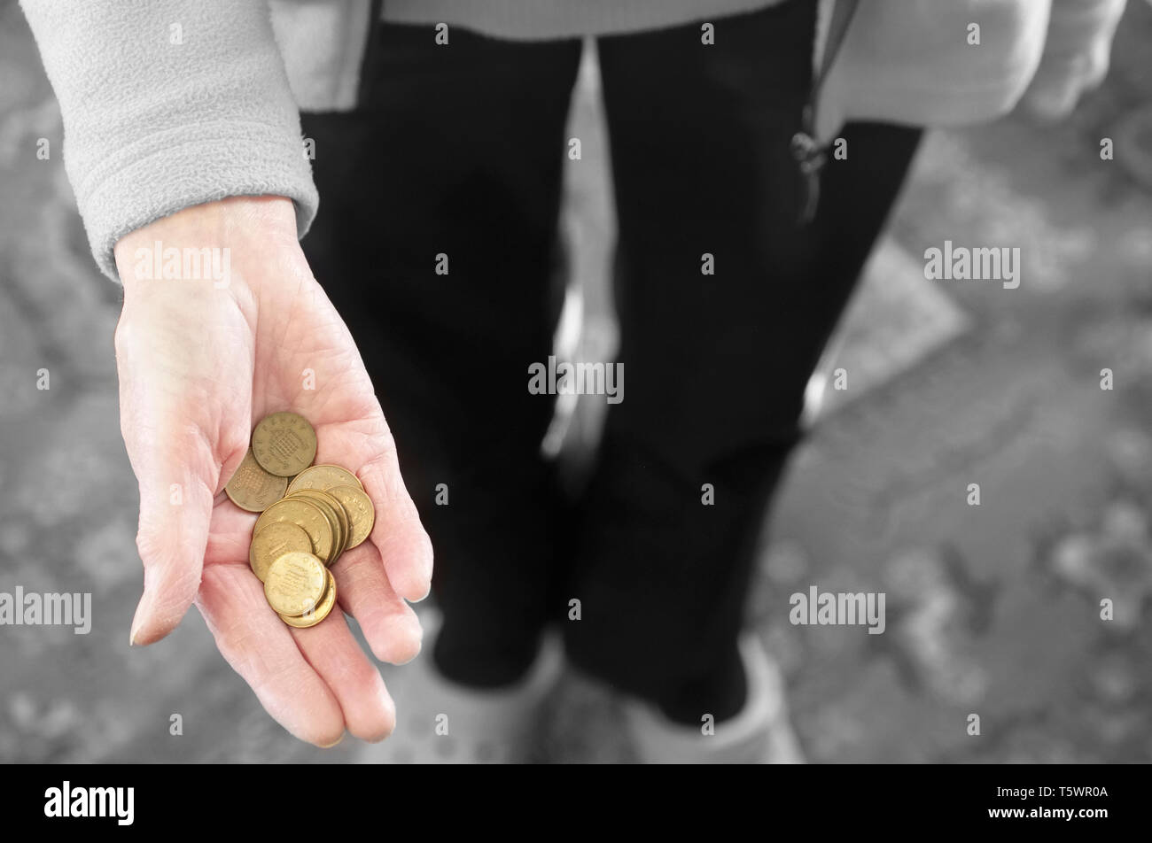 Poor society elderly hand of senior person full of worthless bronze coins - Stock Image