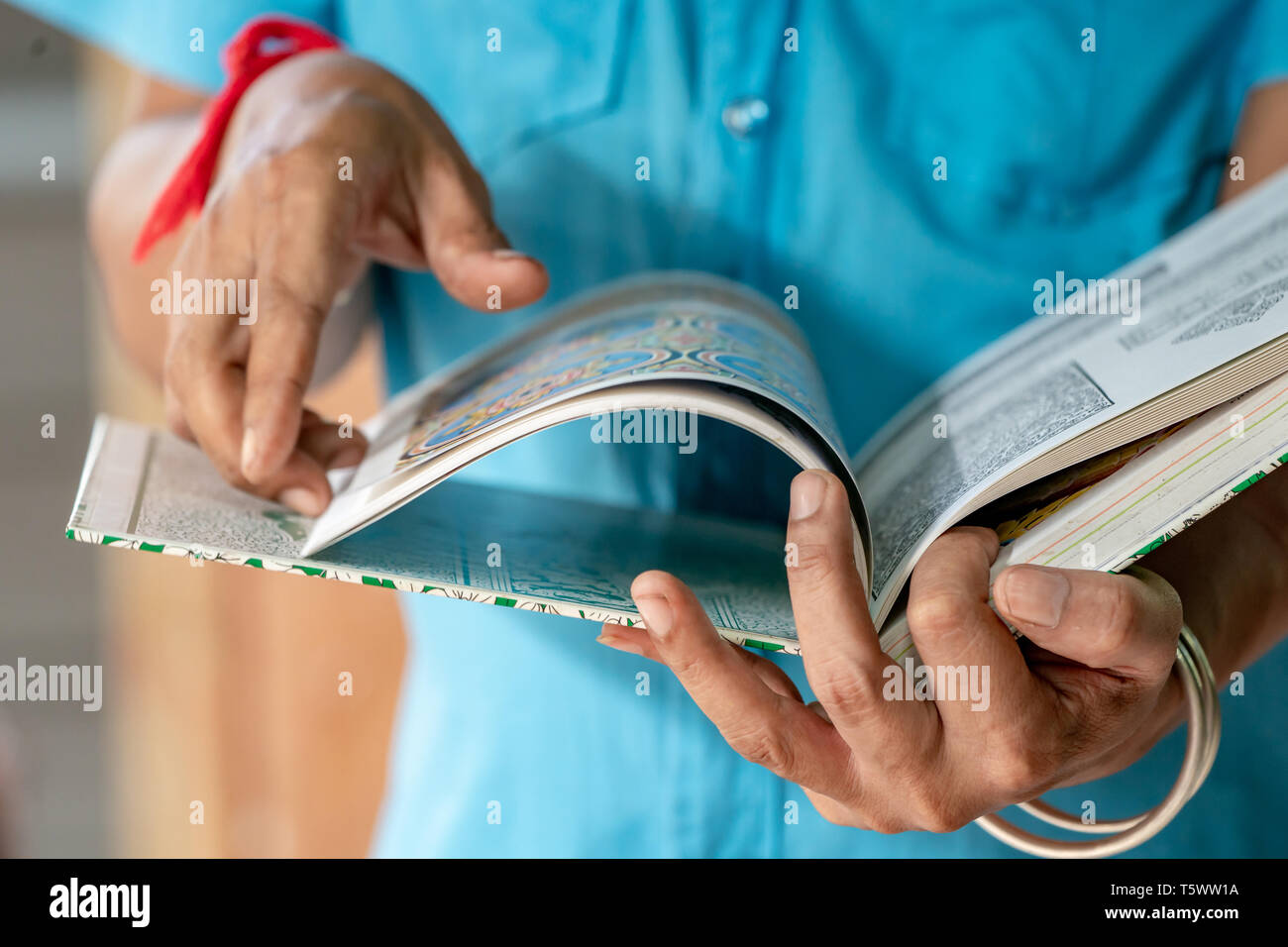 Art man is holding the Thai art book and finding the inspiration for his work. - Stock Image
