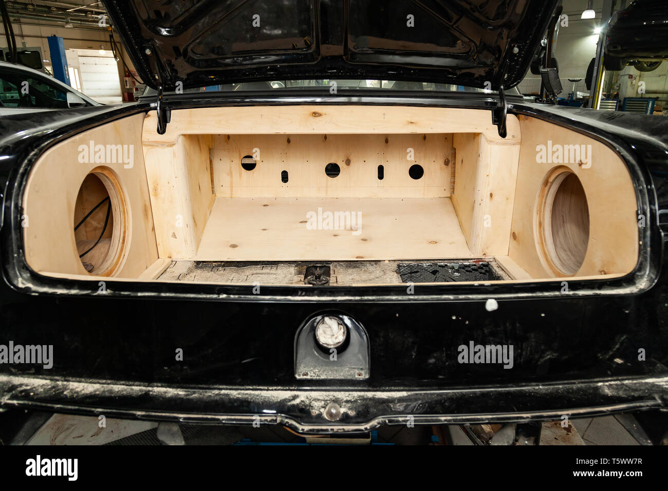 Trunk of a black car sedan with a box made of wood and sawn holes for the installation of subwoofers and speakers for an audio system with a loud soun - Stock Image