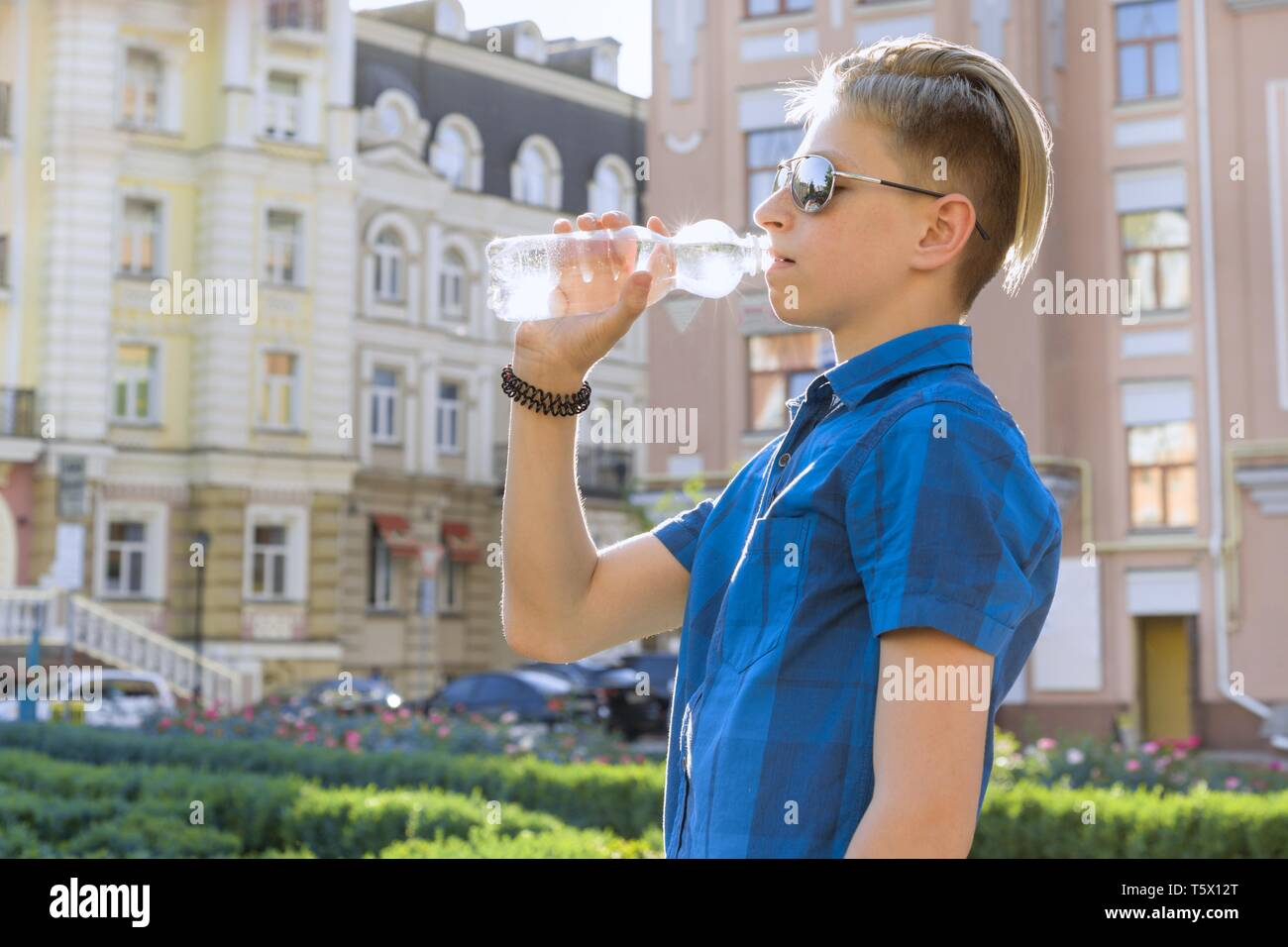 Teenager boy drinking water from bottle on sunny hot summer day in city. - Stock Image