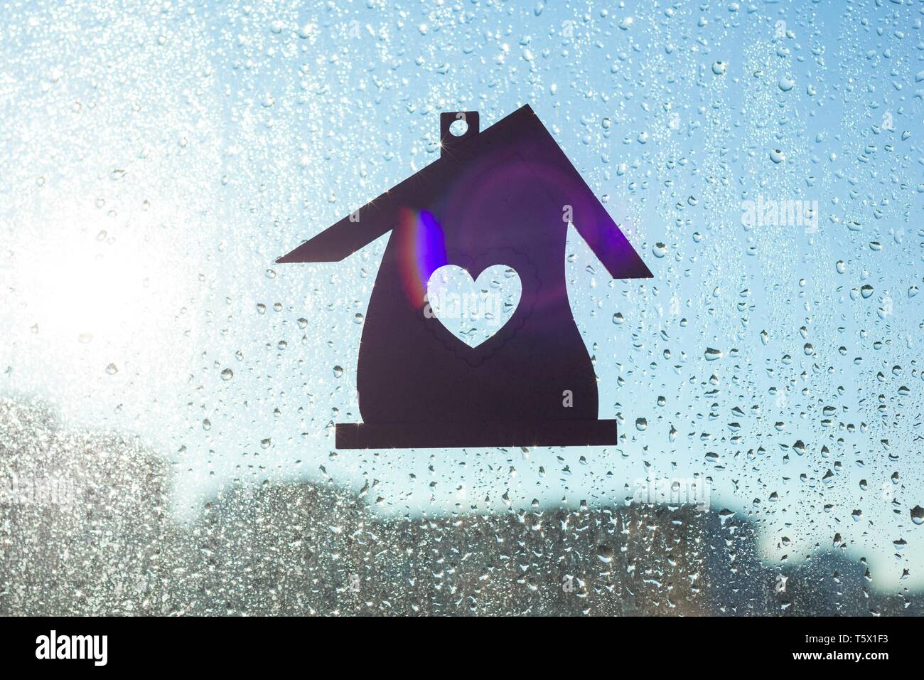 Home Sweet Home. Home symbol with a heart shape on a window background with sunny drops of rain - Stock Image