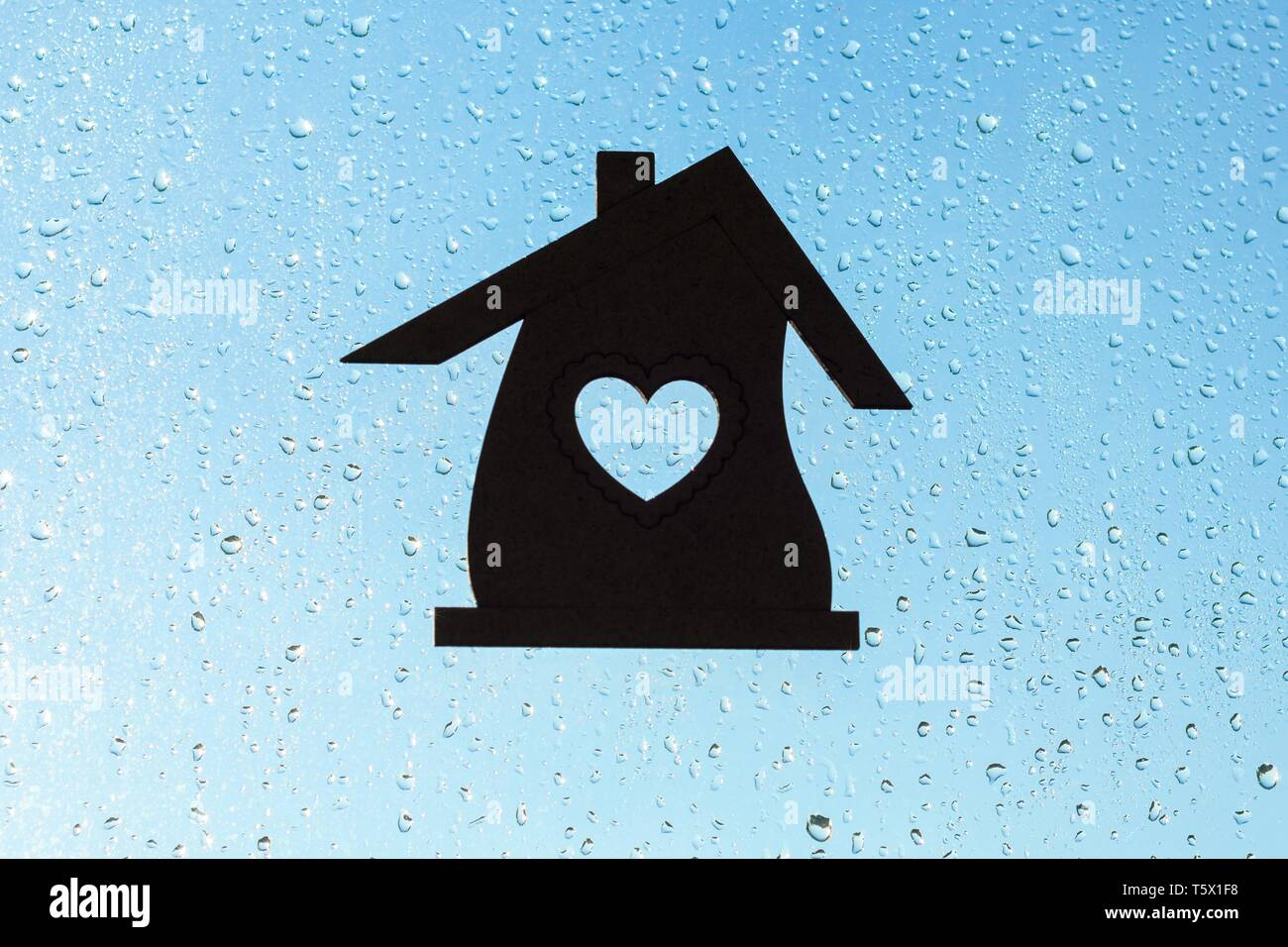 Home Sweet Home. Home symbol with a heart shape on a window background with sunny drops of rain. - Stock Image