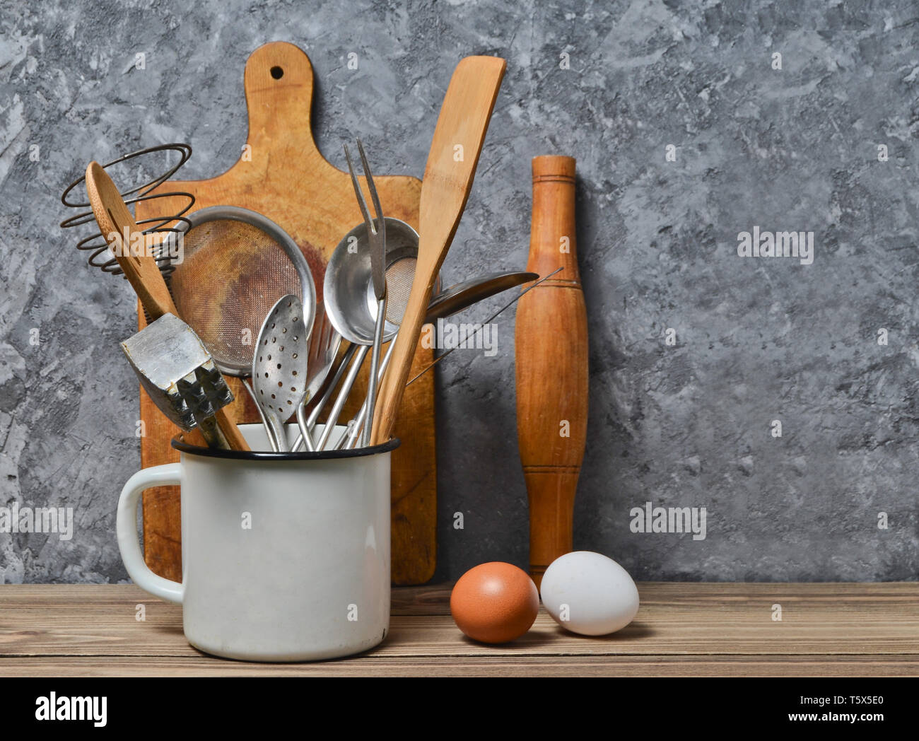 Kitchen tools for cooking on a wooden table on the background of a concrete wall.Copy space. Spoon, forks, wooden spatula, rolling pin, eggs. Stock Photo