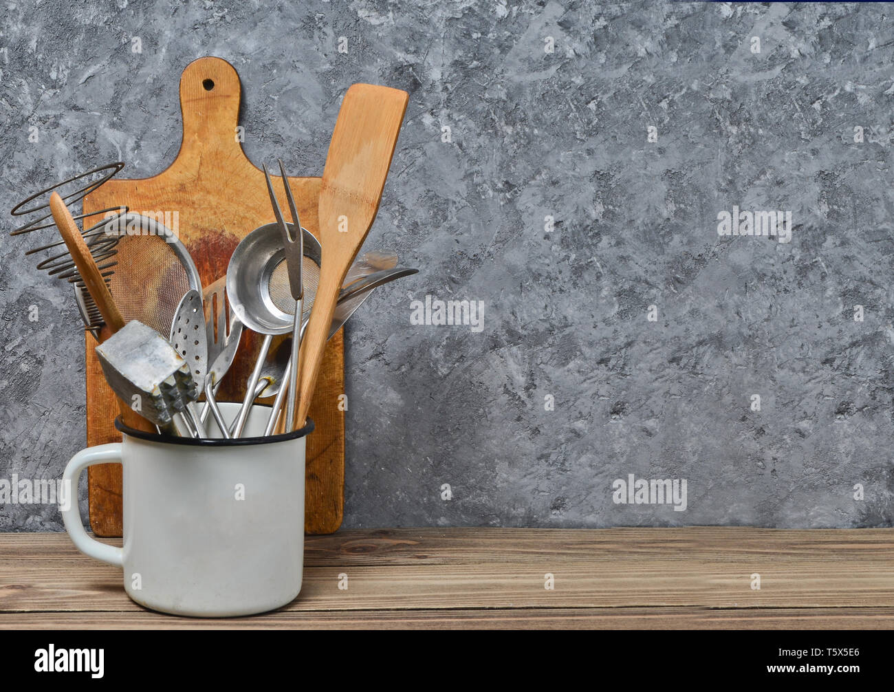 Kitchen tools for cooking on a wooden table on the background of a concrete wall.Copy space. Spoons, forks, wooden spatula. Stock Photo