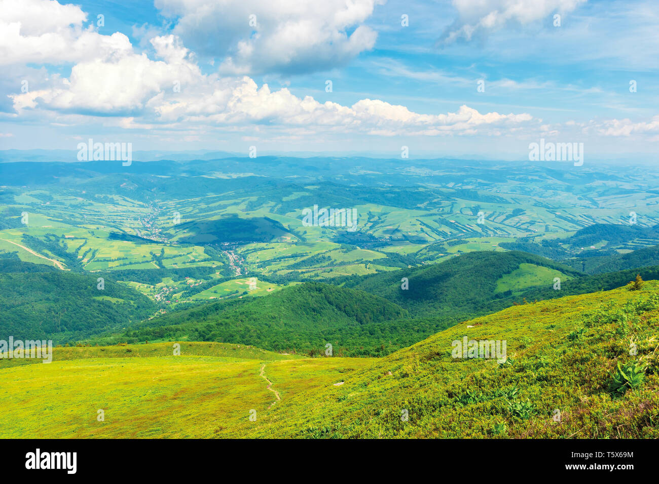 wonderful mountain landscape in summer.  green grassy hills and slopes. path downhill through the meadow. settlement and rural area in the distant val - Stock Image