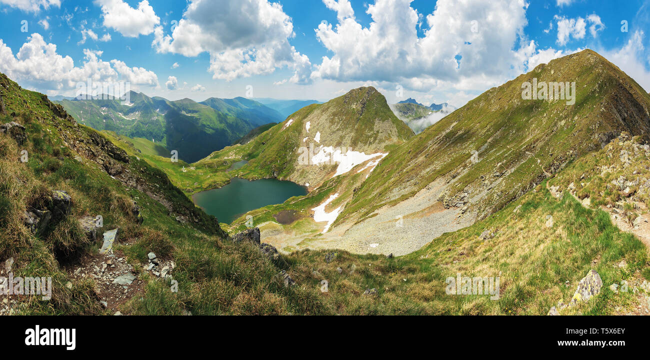 panorama of fagaras mountain in summer. glacier lake capra between hills. beautiful landscape with steep slopes, grassy meadows and peak. wonderful we - Stock Image