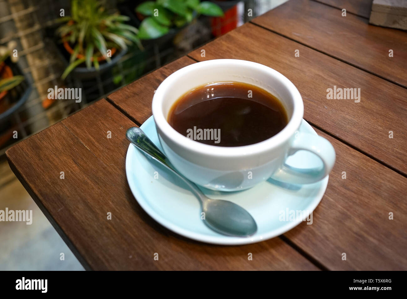 Black coffee, Americano in a cute blue color cup on wooden table - Stock Image