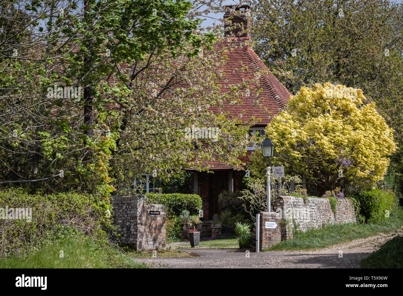 Cozy English Country cottage surrounded by trees - Stock Image