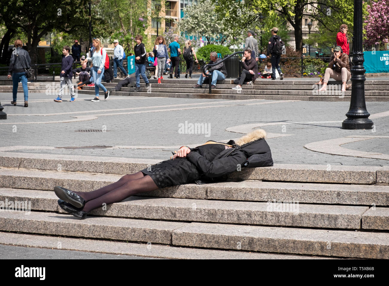 An anonymous well dressed woman in an overcoat sleeping on the steps on Union Square PArk in Lower Manhattan, New York City. - Stock Image