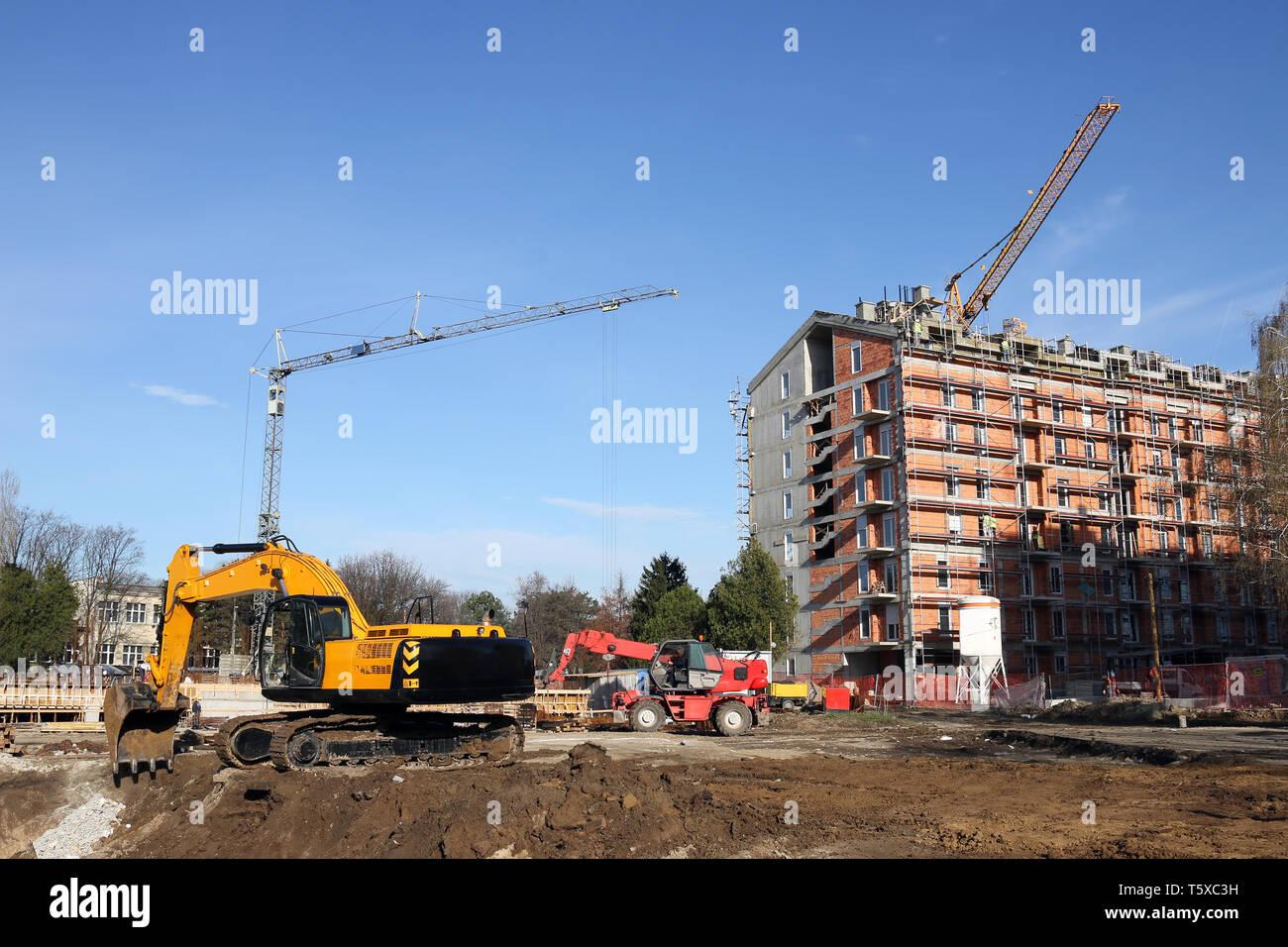 excavators and cranes on construction site - Stock Image