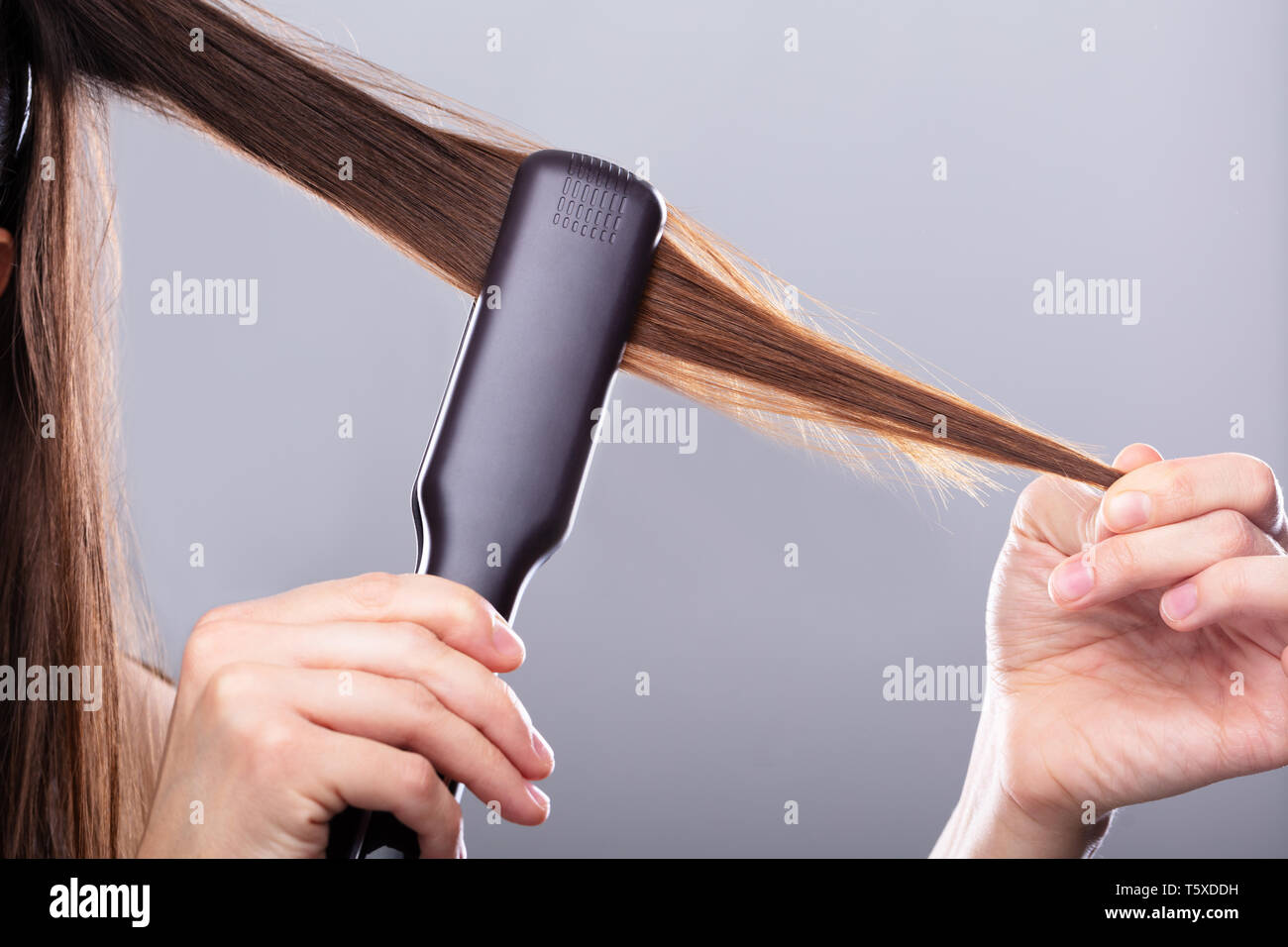 Close-up Of Woman Straightening Hair With Straightener Against Gray Background - Stock Image