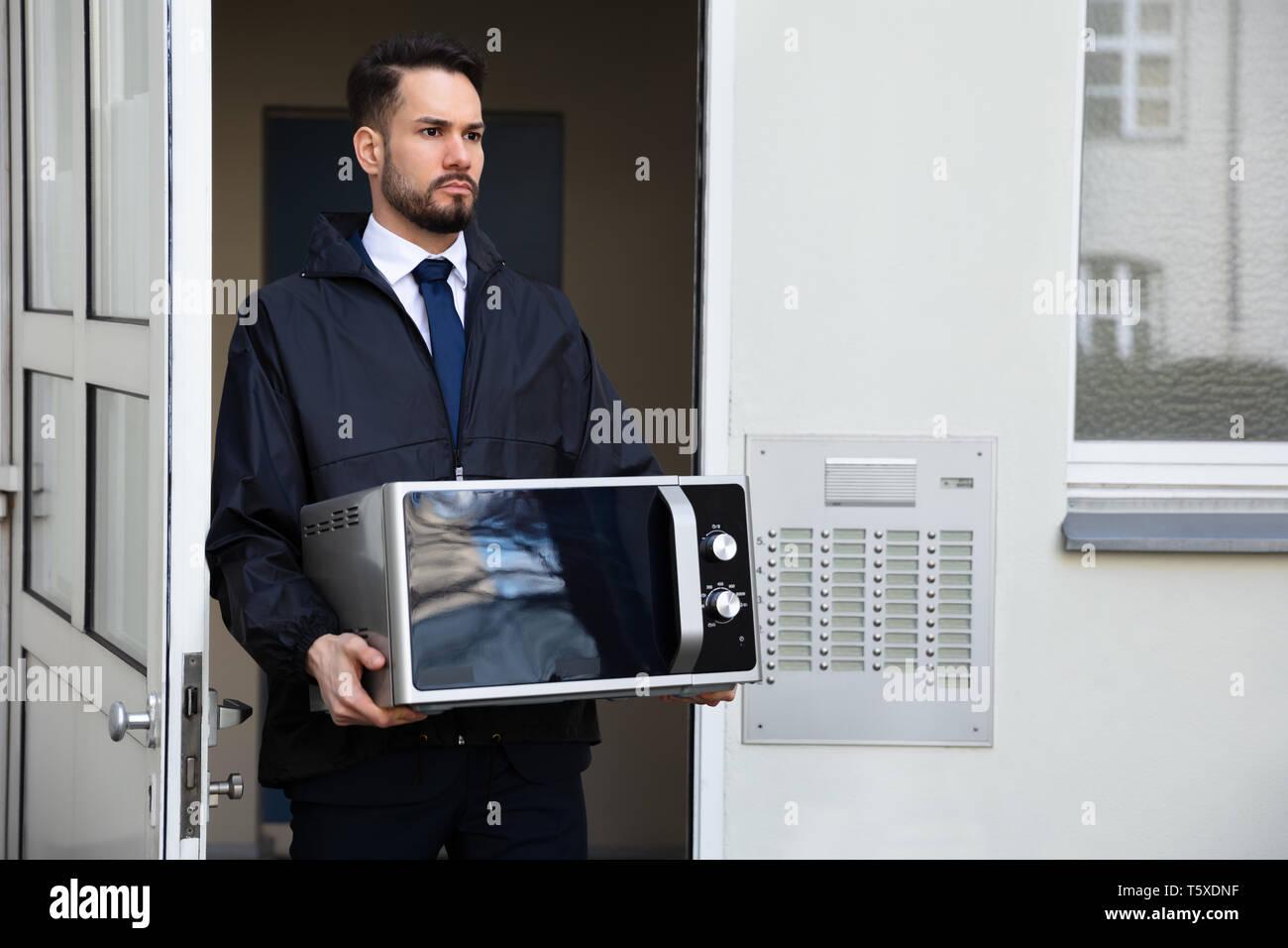 Male Technician Holding Microwave Standing Near Intercom - Stock Image